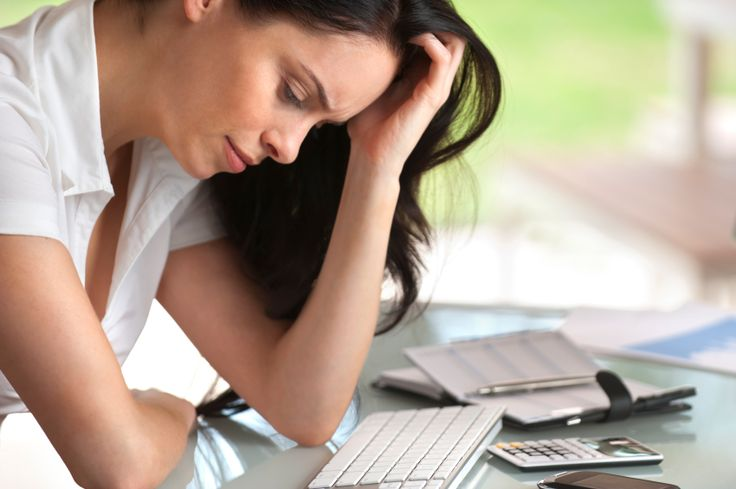 Woman looking stressed at her desk, close up